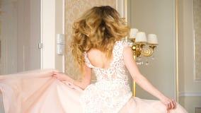 Portret van mooie jonge bruid Een meisje stelt in een hotelruimte De dame spint in haar huwelijkskleding stock footage