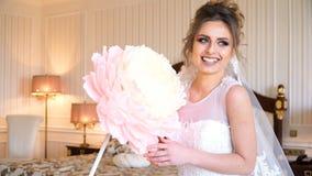 Portret van mooie jonge bruid Een meisje stelt in een hotelruimte Een dame zit met een document bloem door het venster stock videobeelden