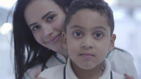 Portret van mooie jonge caucasionvrouw met het knappe mulatjongen kijken die in camera glimlachen Het kind heeft stethoscoop stock footage
