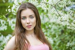 Portret van mooie jonge donkerbruine vrouw in de lentebloesem Royalty-vrije Stock Afbeelding