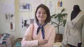 Portret van mooie jonge naaister, die in een naaiende studio glimlacht stock video