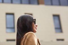 Portret van mooie jonge onderneemster openlucht over vage straatachtergrond Het profiel van elegant donkerbruin wijfje, draagt be stock foto's