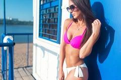Portret van mooie jonge vrouw in bikini bij strand het stellen Royalty-vrije Stock Afbeeldingen
