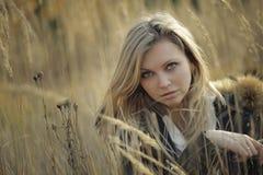 Portret van mooie jonge vrouw die met make-up in hoog gras de camera bekijken Royalty-vrije Stock Foto's