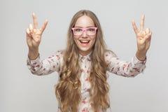 Portret van mooie jonge vrouw die vredesteken tonen en toothy royalty-vrije stock foto