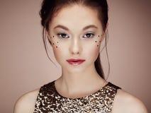Portret van mooie jonge vrouw in een glanzende gouden kleding stock afbeelding