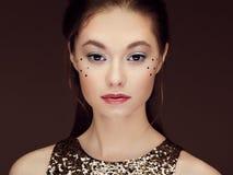 Portret van mooie jonge vrouw in een glanzende gouden kleding stock foto's