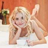 Portret van mooie jonge vrouw met kop op bed Stock Foto's