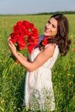 Portret van mooie jonge vrouw met papavers op het gebied met een papaversboeket Royalty-vrije Stock Afbeelding