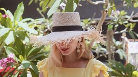Portret van mooie jonge vrouw met strohoed op een zonnige dag die camera bekijken stock video