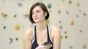 Portret van mooie jonge vrouw met telefoon dichtbij muur voor het beklimmen stock footage
