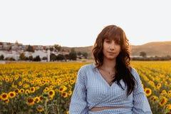 Portret van mooie jonge vrouw met zwart haar op een gebied van zonnebloemen bij zonsondergang stock fotografie