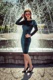 Portret van mooie jonge vrouw status dichtbij fontein stock foto's