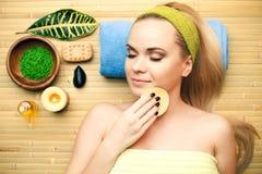 Portret van mooie jonge vrouw wat betreft haar gezicht met spons Stock Foto's