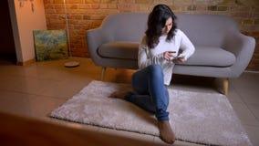 Portret van mooie Kaukasische donkerbruine onderneemsterzitting op vloer en thuis het letten zorgvuldig op in smartphone stock videobeelden