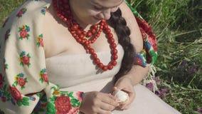 Portret van mooie Kaukasische te zware vrouw die in traditionele kleren in gras zitten die het ei van shell schoonmaken stock videobeelden