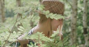 Portret van mooie Kaukasische vrouw in een bos dragende hoed die aan een camera glimlachen stock video
