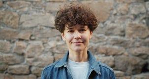 Portret van mooie krullend-haired vrouw die camera bekijken die in openlucht glimlachen stock video