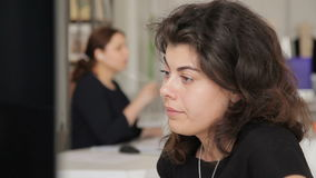 Portret van mooie krullend-haired vrouw met het doordringen die monitor bekijkt stock footage