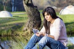 Portret van mooie lachende vrouw die haar geld in het park tellen Stock Foto