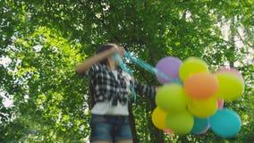 Portret van mooie meisjesspelen met kleurrijke ballons in zonnig park stock video