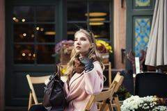 Portret van mooie modieuze jonge vrouwenzitting in straatkoffie Het model opzij kijken De Levensstijl van de stad Vrouwelijke man stock foto's
