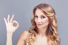 Portret van mooie nlondhairvrouw die het o.k. die gebaar en knipogen tonen over blauwe achtergrond wordt geïsoleerd Royalty-vrije Stock Foto