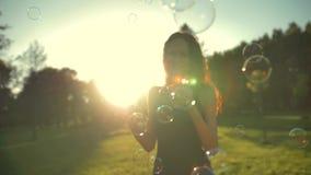 Portret van mooie redhair jonge vrouw Blazende bel in het park stock video