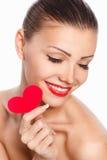 Portret van Mooie schitterende glimlachende vrouw met glamour heldere make-up en rood hart ter beschikking Royalty-vrije Stock Foto's