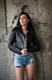 Portret van mooie sexy jonge vrouw met jeans, het witte jasje van het onderhemd zwarte leer, op stedelijke achtergrond Royalty-vrije Stock Afbeeldingen