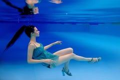 Portret van mooie slanke modieuze donkerbruin in blauwe kleding en hielenschoenen onderwater royalty-vrije stock afbeeldingen