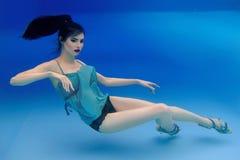 Portret van mooie slanke modieuze donkerbruin in blauwe kleding en hielenschoenen onderwater royalty-vrije stock foto's