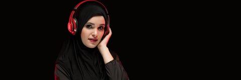 Portret van mooie slimme jonge moslimvrouw die zwarte hijab dragen die aan muziek in hoofdtelefoons met copyspace luisteren royalty-vrije stock foto