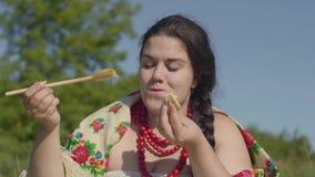 Portret van mooie te zware vrouw die pannekoeken met honing in openlucht eten Gezond eigengemaakt voedsel, verbinding met stock video