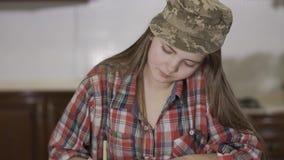 Portret van mooie tiener in geruit overhemd en militaire hoed op het hoofd die een brievenzitting schrijven thuis bij stock videobeelden