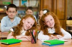 Portret van mooie tweelingenmeisjes met schooljongens op achtergrond Lo Stock Afbeeldingen