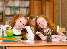 Portret van mooie tweelingenmeisjes met schoolmeisje op achtergrond Stock Foto