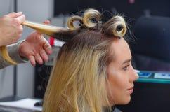 Portret van mooie vrouw in een haarsalon met een stilist die met krulspelden in het hoofd, op een achtergrond van de haarsalon we royalty-vrije stock afbeeldingen