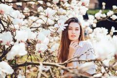 Portret van mooie vrouw met magnoliabloemen De de lentetijd… nam bladeren, natuurlijke achtergrond toe royalty-vrije stock afbeelding