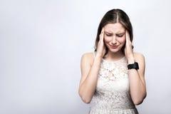 Portret van mooie vrouw met sproeten en wit kleding en slimme horloge met hoofdpijnpijn op zilveren grijze achtergrond stock fotografie