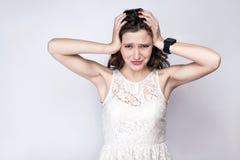 Portret van mooie vrouw met sproeten en wit kleding en slimme horloge met hoofdpijnpijn op zilveren grijze achtergrond royalty-vrije stock foto