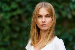 Portret van mooie vrouw op groene bomen als achtergrond Royalty-vrije Stock Foto