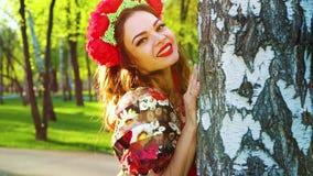 Portret van mooie vrouw in volks gestileerd kostuum die uit van berk gluren stock video