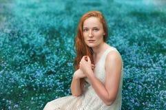 Portret van mooie vrouwenzitting op de weide met Royalty-vrije Stock Fotografie