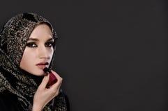 Portret van Moslimvrouw die haar lippen met een lippenstift schilderen stock afbeelding