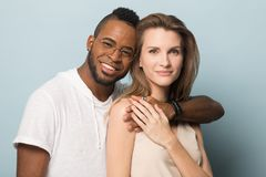 Portret van multiraciale paaromhelzing die camera bekijken stock foto