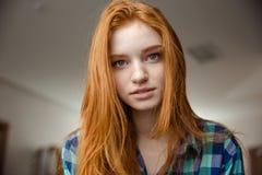 Portret van nadenkende aantrekkelijke roodharige jonge vrouw in plaidoverhemd Stock Fotografie