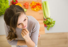 Portret van nadenkende jonge vrouw in keuken stock foto