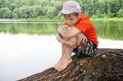 Portret van nadenkende jongen door rivier Royalty-vrije Stock Foto's