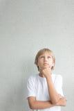 Portret van nadenkende jongen met gekruiste wapens die omhoog eruit zien Royalty-vrije Stock Fotografie